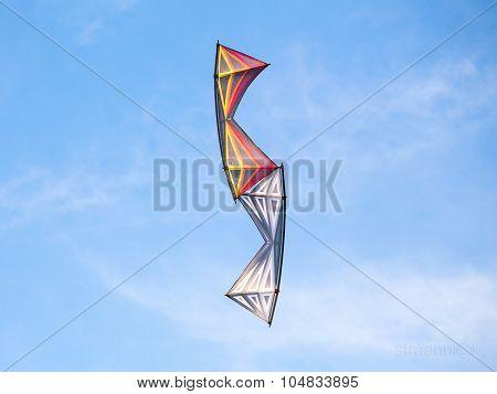 Pair of stunt kites perform aerobatics in the blue sunny summer sky at the kites festival