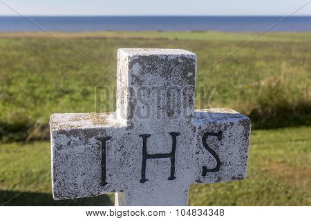 concrete gravestone cross with IHS letters