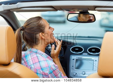 Woman Corrects Makeup Looking In The Rearview Mirror In A Convertible