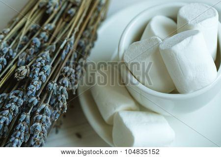 Marshmallow In A Cup And Lavender On A White Wooden