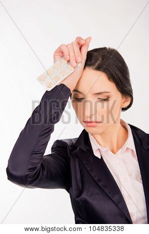 Feeling Headache. Frustrated Young Woman Holding Headache Tablets