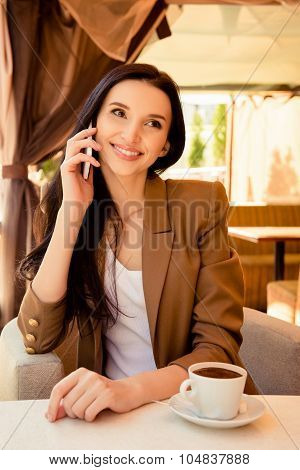 Charming Young Woman Talking On Phone At Dinner With Cup Of Coffee
