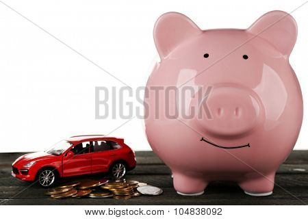 Piggy bank style money box on wooden table, isolated on white