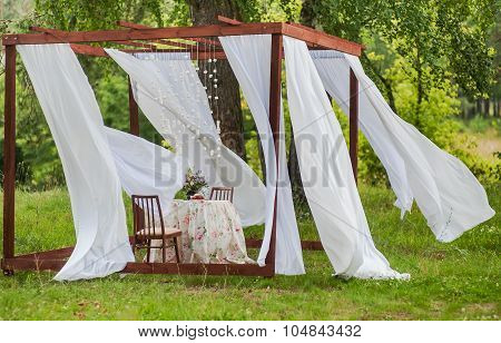 Outdoor gazebo with white curtains. Wedding decorations. Art object.