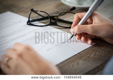 Closeup shot of a woman signing a form. She's writing on a financial contract. Shallow depth of field with focus on tip of the pen.