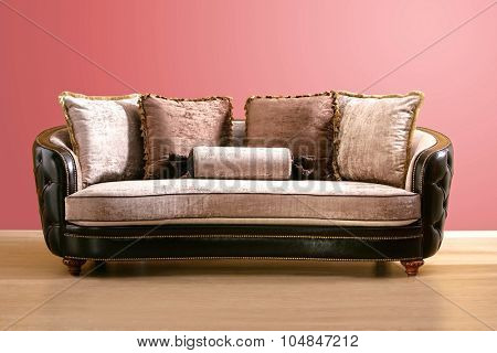 vintage couch , made of brown leather and pink velvet fabric with burgundy and pink pillow, isolated into an empty room