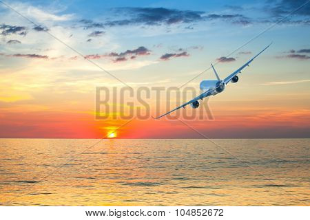 Jumbo jet airplane flying above tropical sea at beautiful sunset.