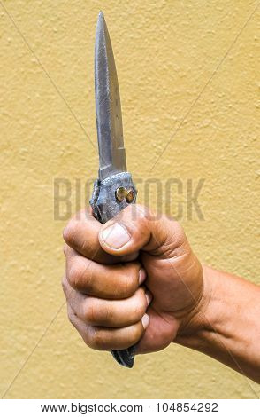 Hand holding a knife on yellow background