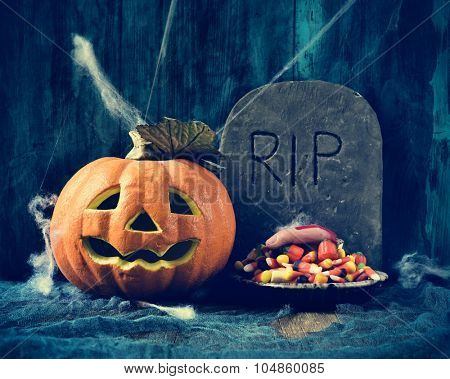 a plate with Halloween candies and an amputated finger in a dismal scene with a carved pumpkin and a gravestone with the text RIP carved in