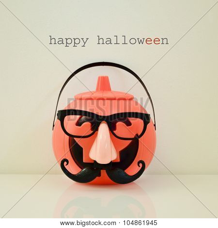 a carved pumpkin disguised with a fake nose, a moustache and black eyeglasses, and the text happy halloween