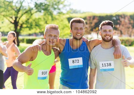 fitness, sport, friendship, gesture and healthy lifestyle concept - group of happy teenage friends or sportsmen with racing badge numbers showing thumbs up at marathon outdoors