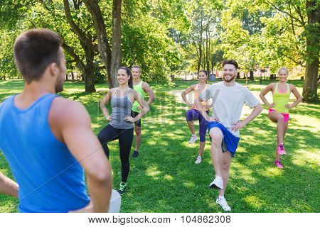 fitness, sport, friendship and healthy lifestyle concept - group of happy teenage friends or sportsmen exercising and raising legs at boot camp