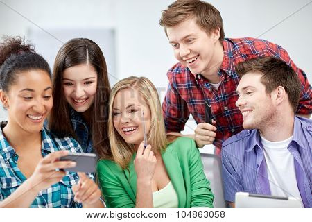 education, people, friendship, technology and learning concept - group of happy international high school students or classmates with smartphone in classroom