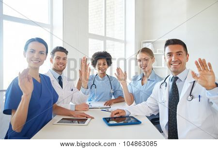 medical education, health care, gesture, people and medicine concept - group of happy doctors meeting and waving hands at hospital