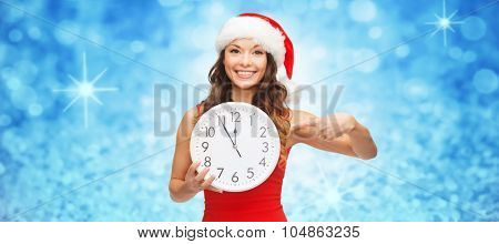 christmas, winter, holidays and time concept - smiling woman in santa helper hat with clock showing twelve over blue glitter or lights background