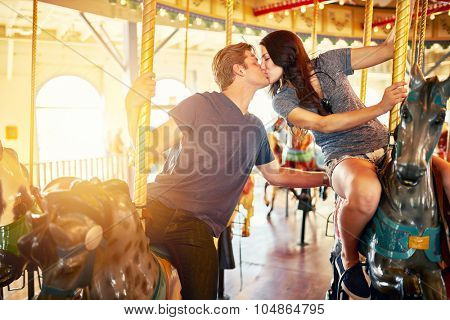 romantic couple kissing on merry go round shot with lens flare, selective focus, and blurred motion from action