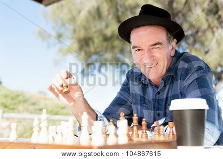 Elderly man sitting outdoors with chess