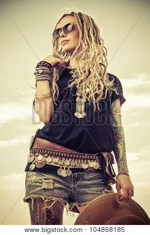 Fashion shot of a beautiful boho style girl over sky background. Boho, hippie.