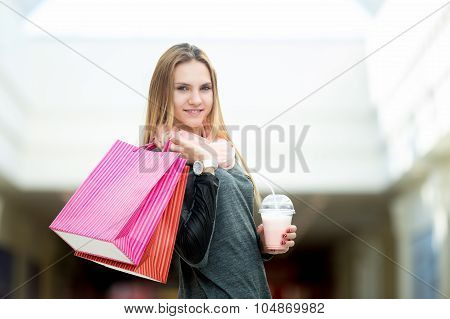 Young Woman In Supermarket With Shopping Bags And Strawberry Cocktail
