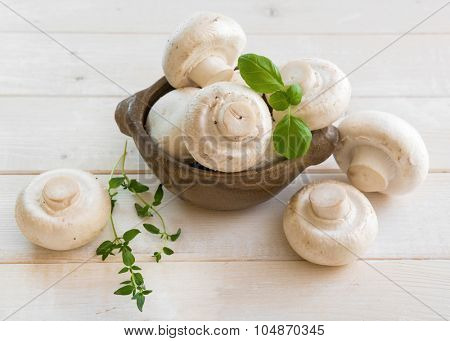 Fresh whole white button mushrooms on a wooden background