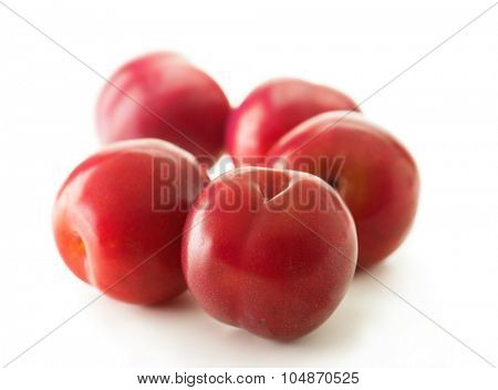 Ripe fresh harvested plums, isolated on white. Three red plums on white surface. Focus on forehand plum. Shallow depth of field.