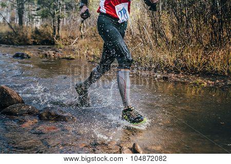 feet closeup male runner crossing river on rocks