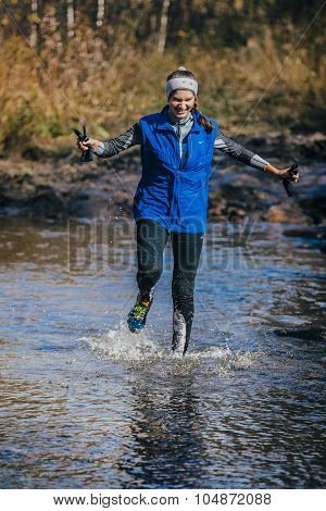 young girl athlete crossing a mountain river