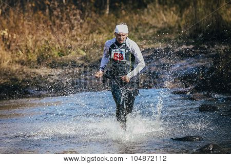 runner middle-aged man crossing river, and around him water splashes