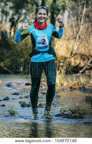 young woman runner smiling while crossing a mountain river