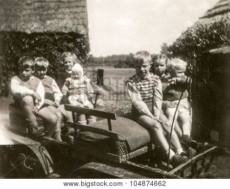 ANIELIN, POLAND, CIRCA 1955: Vintage photo of group of little children sitting on cart