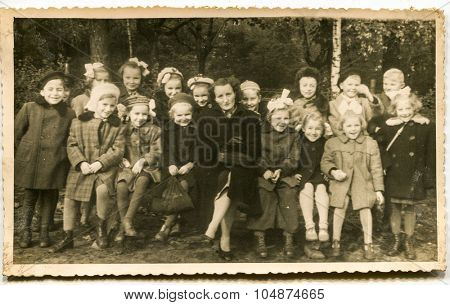 LODZ, POLAND, CIRCA 1940: Vintage photo of group of little school children posing with their tutor