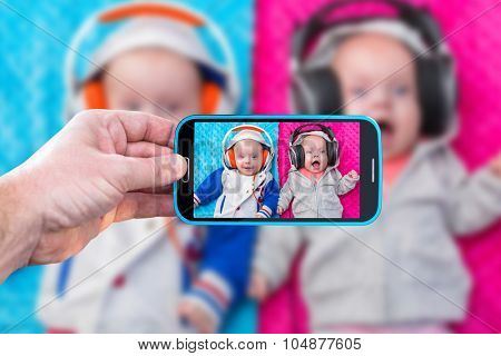 Hand with smartphone making photo of baby twins with headphones