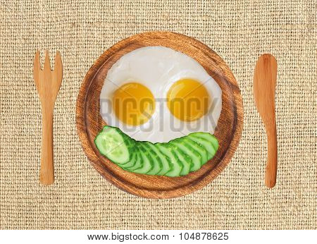 Fried Eggs And Fresh Cucumber On Wooden Plate, Fork And Knife On The Llinen Texture Background
