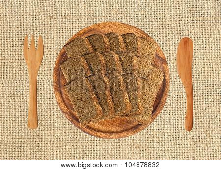 Slice Of Black Rye Bread On Wooden Plate, Fork And Knife On The Llinen Texture Background