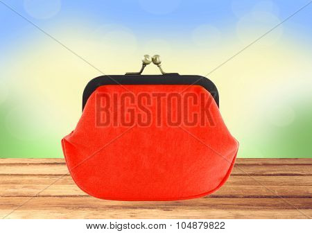 Red Purse On Wooden Table Over Bright Nature Background