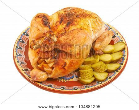 Fried Chicken On A Plate With Pickles On A White