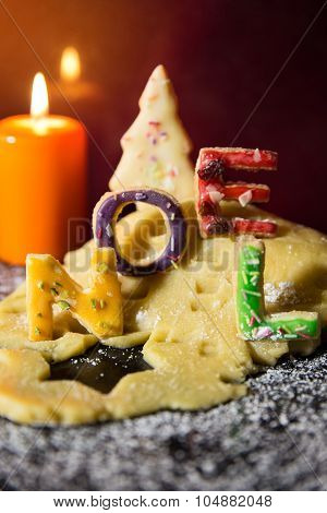 Cookie Letters With Cookie Dough And A Candle, Word Noel In Front Of Black Background
