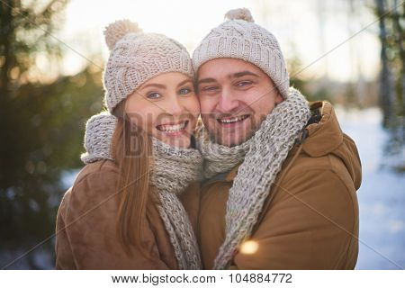Joyful sweethearts in winterwear looking at camera outdoors