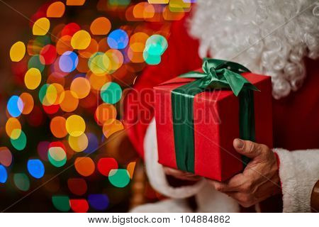 Red giftbox bound with green ribbon in Santa hands