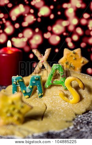 Cookie Letters With Cookie Dough And A Candle, Word Xmas With Stars In Front Of Sparkle Background
