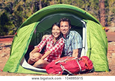 Happy young couple sitting in tent. Male and female hikers are resting in tent. Young partners are with hiking bag on sunny day.
