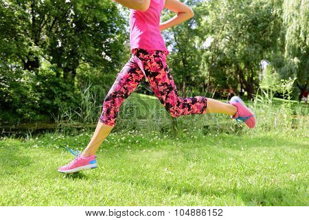 Female runner running shoes and legs in city park. Woman jogging wearing floral capris leggings compression tights and pink running shoes.