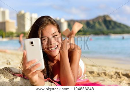 Smartphone woman using smart phone app on Waikiki Beach smiling laughing having fun. Girl sms text messaging or browsing on internet smiling happy outdoors. Mixed race Asian Caucasian on Oahu, Hawaii.