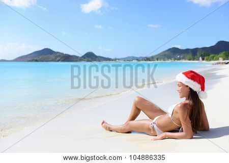 Christmas beach woman in santa hat and bikini on holidays travel vacation getaway relaxing on beautiful tropical beach with turquoise water in the Caribbean. Beautiful young female model sun tanning.