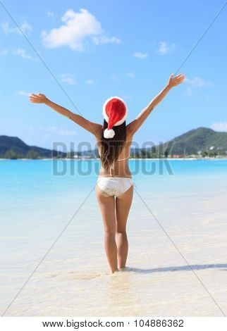 Christmas Santa hat bikini woman on beach holidays travel vacation getaway. Girl free and happy with arms raised up of joy on tropical Caribbean beach. Beautiful girl in bikini having fun in the sun.