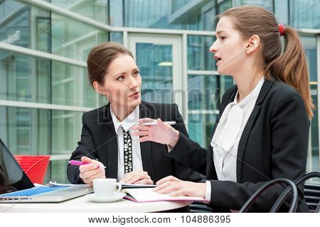 Two young business women works together
