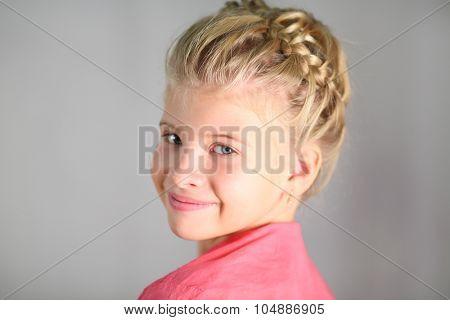 Portrait of a little girl with a pigtail on her head isolated on gray