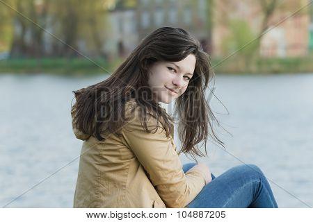 Portrait of turning around student girl wearing beige demi-season jacket at city park lake backgroun