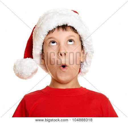winter holiday christmas concept - boy in santa hat look up on white isolated