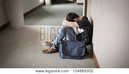 Depressed male student with head on knees sitting by wall in college